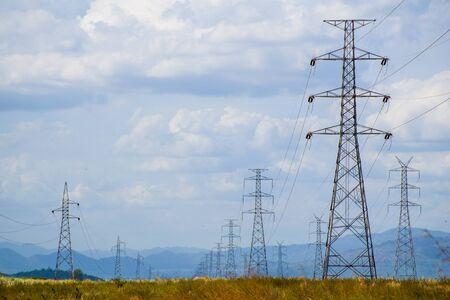 Poste de alta tensión Torre de alta tensión Ubicada en un campo marrón que tiene fondo de montaña y cielo. Foto de archivo