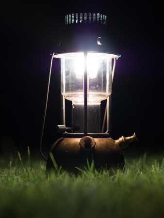 Ancient lamps illuminated with oil on the grass at night. Archivio Fotografico