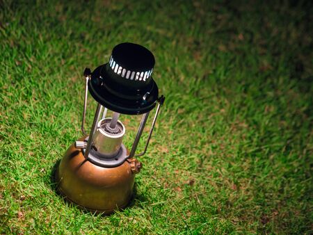 vintage kerosene oil lantern lamp burning with a soft glow light On the green lawn at night.