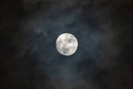 Full moon on the dark night shining on the sky in cloudy day.