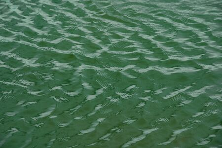 green water surface By wind.Water surface ruffled by light wind with small waves running diagonally, with reflections and graduated from light and green tones.soft focus. 写真素材 - 129954069