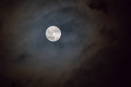 Full moon on the dark night shining on the sky in cloudy day. 写真素材 - 129955792