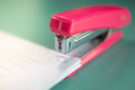 pink stapler does not pierce through many sheets of paper. shallow focus effect. 写真素材