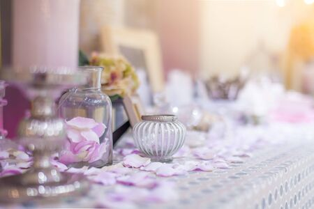 Beautiful vanity with purple flower petals and perfume bottles.dressing on table for makeup.shallow focus effect.