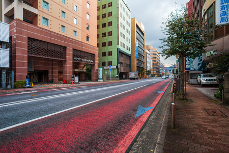Kitakyushu, Japan - November 22, 2016 : Cars in Kitakyushu, Fukuoka Prefecture, Japan, City Road, with a few cars and small number of pedestrians In the morning the rain is going to fall in the fall. 新聞圖片