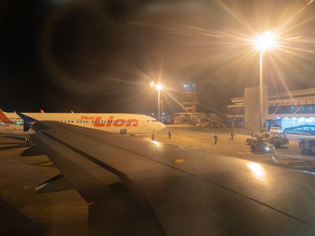 Udon Thani, Thailandia - 17 dicembre 2017: Parcheggio aereo sull'aeroporto internazionale di Udon Thani, Thailandia, Thai Lion Airlines e la fiera della luce del pilastro ad alta luce all'aeroporto di notte. Editoriali