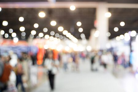 Blurred images of trade fairs in the big hall. image of people walking on a trade fair exhibition or expo where business people show innovation activity and present product in a big hall. 写真素材