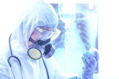 coronavirus or covid-19 concept,Male doctor in a protective suit Giving medicines to patients in the hospital.Lung X-ray Film Destruction Background.shallow focus effect.