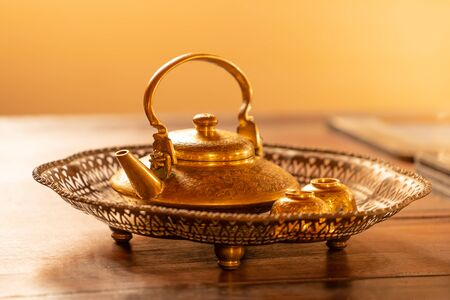 Golden tea pot in antique brass tray on wooden table, antique gold teapot,Traditional Thai style.shallow focus effect. 写真素材