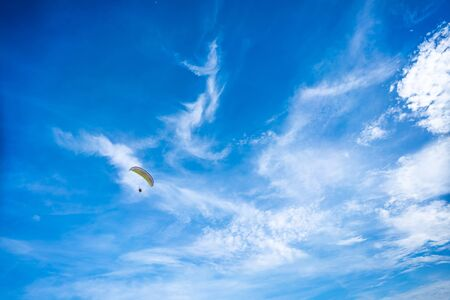 Fly on paramotor On the blue sky and white clouds