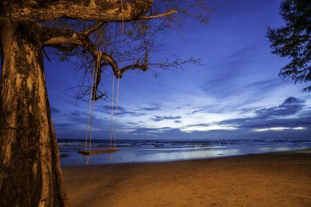 Swing under the tree By the beach at the sea At dusk, the sun has set,Chanthaburi Coast, Thailand.soft focus.