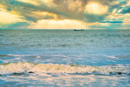 Shallow depth of field shot of Sea water Blurred white wave bubble images and Golden evening sky.at Chanthaburi Coast, Thailand.soft focus.