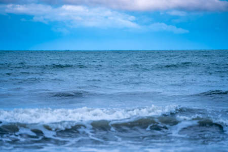 Shallow depth of field shot of Sea water Blurred white wave bubble images and a blue sky with white clouds.at Chanthaburi Coast, Thailand.soft focus.