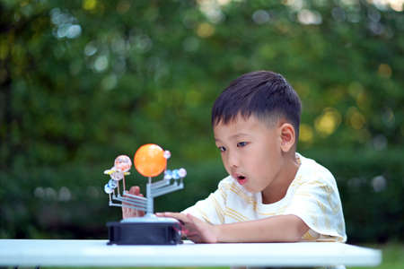 Asian boy Living Solar System Toys, Home Learning Equipment, during new normal change after coronavirus or post covid-19 outbreak pandemic situation