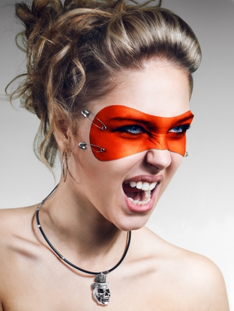Girl in orange leather mask screaming on white-gray gradient background photo