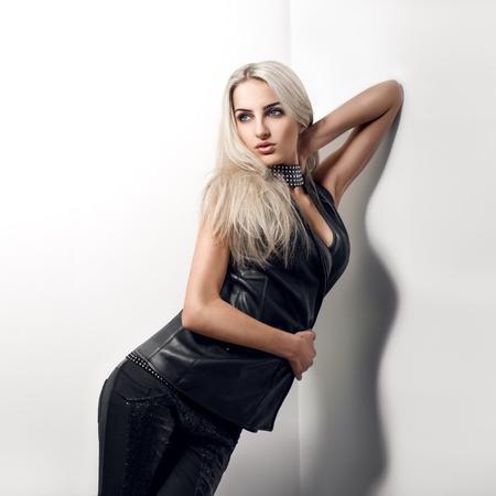 sexy blonde is in the corner in studio photo