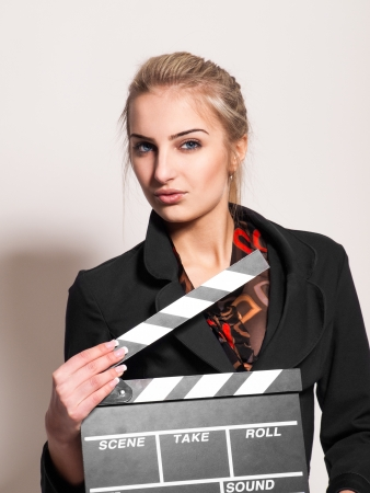 portrait of pretty girl with film slate in studio on gray background photo