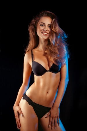 Beauty woman in black lingerie smiling at camera in studio on black background photo