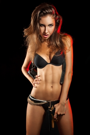 Hot woman with gun in studio on black background photo