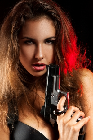 Portrait of woman with pistol in studio on black background photo