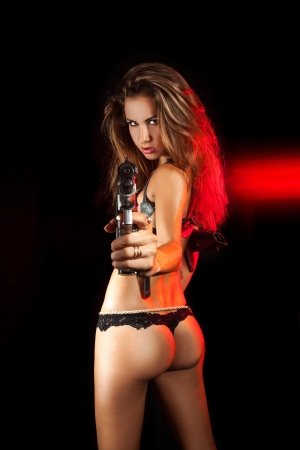 Sexy woman with pistol from behind with red lights in studio on black background photo
