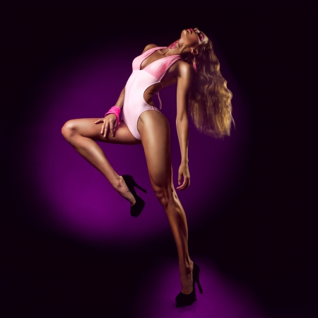 Female in action on purple background in studio photo
