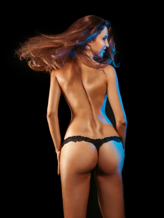 adult female in black panties shooting from behind in studio on black background photo