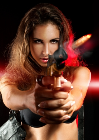 Attractive woman shooting from golden gun in studio photo