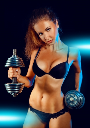 Caucasian sports female in black lingeris with dumbbells in studio on black background photo