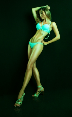 Full length portrit of pretty female in green tones in studio on black background photo