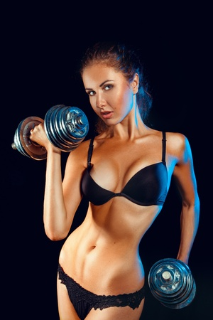 Hot sports girl woth dumbbells looking at camera in studio on black background photo