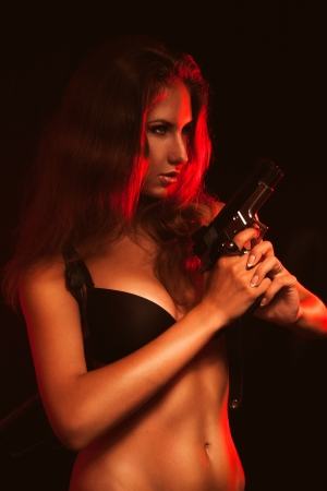 Hot woman in black bra and gun in studio photo