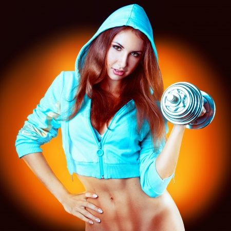 inflated girl with dumbbells in a sports jacket in studio on yellow background photo