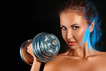 Portrait of girl with dumbbells in hand in studio on black background photo
