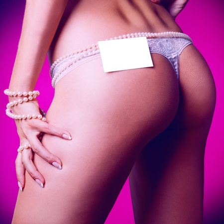 Square photo of female ass in white panties and empty name tag in studio photo