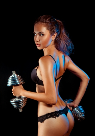 Vertical photo of sports woman in black lingerie and dumbbells in studio on black background photo