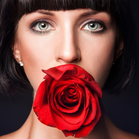 Close up portrait of pretty woman with red rose in mouth photo