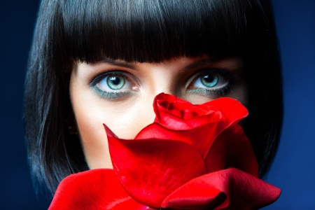 Lovely brunette behind red rose in studio photo