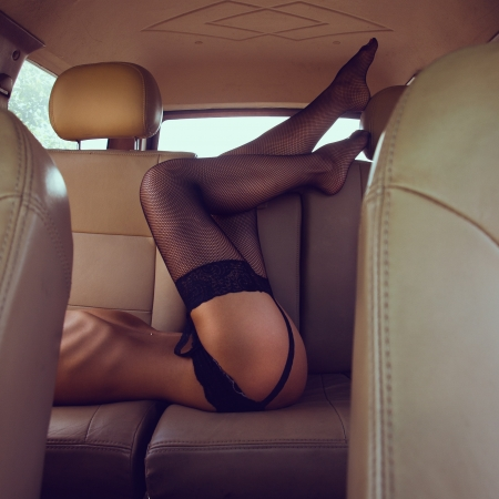 Sexy woman lying in backseat of car photo