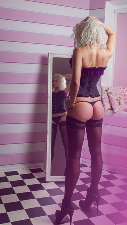 beautiful curly blonde in lingerie looking in mirror photo