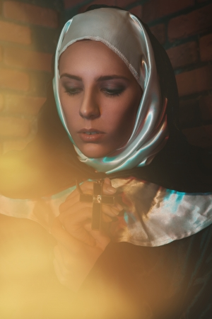 portrait of pretty nun near brick wall photo