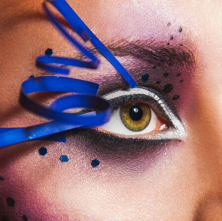 Close up photo of female eye with creative make up in studio photo