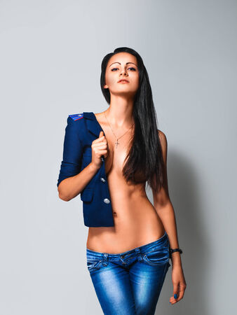 Hot brunette with silicone breast wearing jacket with shoulder straps in studio on grey backogrund photo