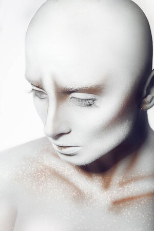 Hairless pretty woman with white paint on body and face in studio photo