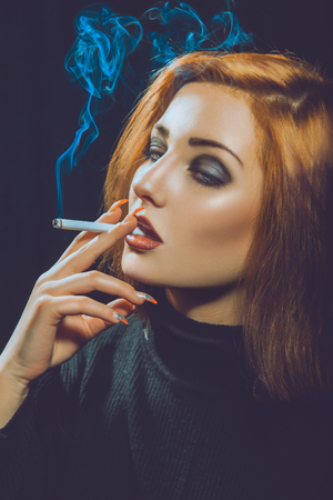 smoking red hair woman in studio on black  photo