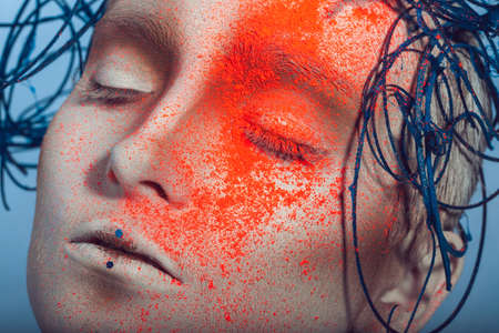 macro portrait of woman with neon powder on face in studio photo