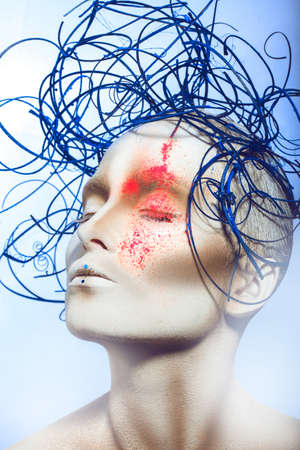 portrait of gorgeous female with body art and neon powder on face in studio photo