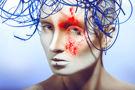 sexual woman with body art and neon powder in studio on blue background photo