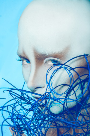 Attractive bald woman with body art on blue background in studio photo