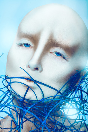 bald girl with body art on blue background in studio photo